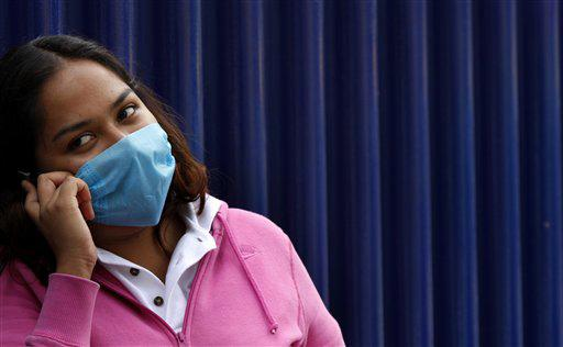 A woman wears a face mask as a precaution against swine flu as she speaks on a cell phone outside the National Institute of Respiratory Illnesses (INER) where her mother is hospitalized with swine flu-like symptoms in Mexico City, Wednesday, Sept. 23, 2009.