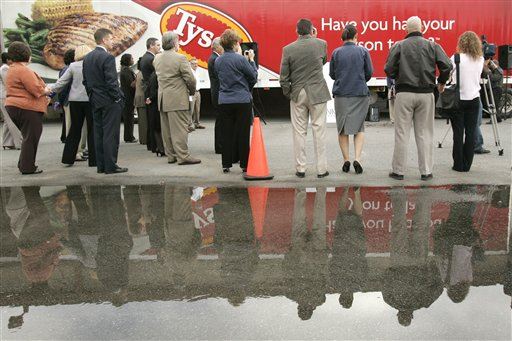 Members of the news media and others gather near a Tyson Foods, Inc., truck parked at Arkansas Foodbank Network in Little Rock, Ark., Wednesday, Oct. 28, 2009. Tyson Foods donated about 15 tons of food in honor of a volunteer of 25 years at an Arkadelphia, Ark., food bank.