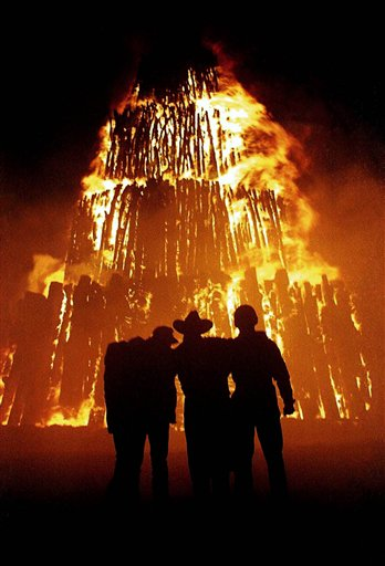 FILE - In this Tuesday, Nov. 26, 1996 file photo, Texas A&M University students huddle in front of a bonfire, in College Station, Texas. The bonfire, which was under construction, collapsed Thursday, Nov. 18, 1999, killing 12.