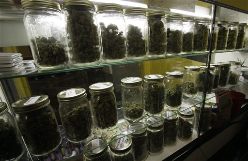 Traditional canning jars hold varieties of marijuana in a cabinet at the La Brea Collective medical marijuana dispensary in Los Angeles Tuesday, Nov. 17, 2009. Los Angeles Countys district attorney says he intends to prosecute owners of marijuana dispensaries that take cash for pot.