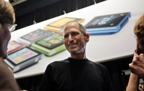 Apple CEO Steve Jobs smiles in front of an iPod Shuffle poster, Wednesday, Sept. 1, 2010, in San Francisco.