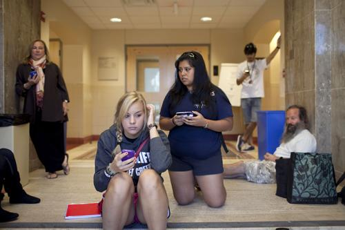 University of Texas Students Paige Raiczyk, Veronica Rivera and other students and faculty hold their phones for updated texts inside Benedict Hall on campus in Austin, Texas during a school shooting Tuesday, Sept. 28.