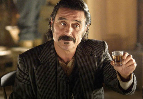 An actor on the set of Deadwood holds up a shot glass. The HBO series is set to be released to Blu-ray this year.