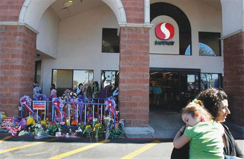A woman leaves the Safeway grocery store, with a makeshift memorial, in Tucson, Ariz. Rep. Gabrielle Giffords, D-Ariz., is still in critical condition after a mass shooting at the location that left six dead on Jan. 15.