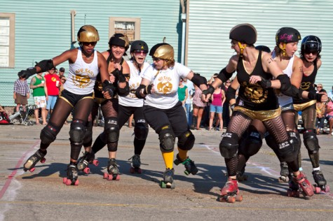 Brooke Ethridge, in white, back, attempts to keep the black team's jammer from breaking through the pack in the Big Easy Rollergirls exhibition bout held April 2 at the Freret St. Festival. Ethridge is a Loyola English instructor by day and a Big Easy Roller Girl by night.