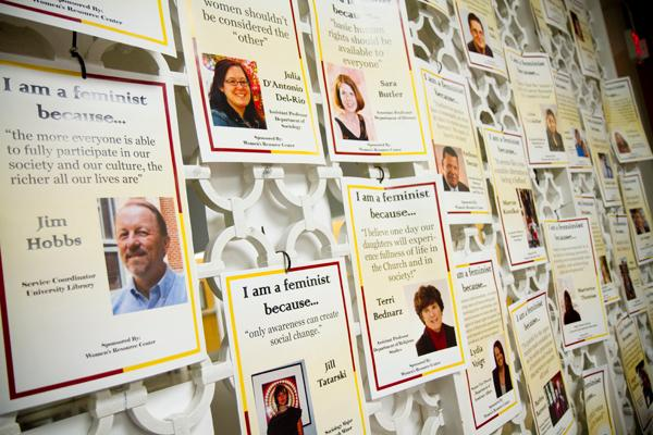 Fliers of students and faculty who support feminism line the wall by the CC's lounge in the Dana Center. The fliers were posted as part of the Women's Resource Center's efforts to raise awareness about  gender equality.