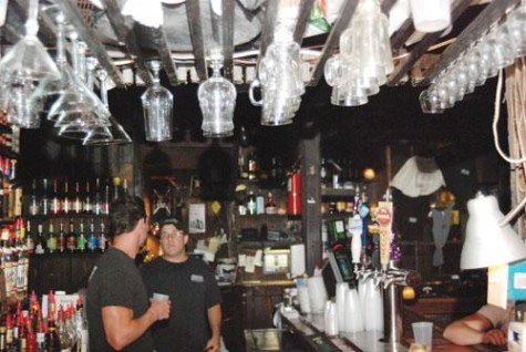 Two bartenders talk at Lafitte's Blacksmith Bar on Bourbon Street while working. Lafitte's is one of the oldest bars in New Orleans.