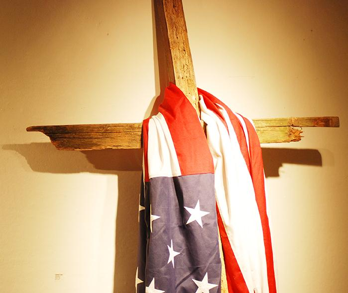An+American+flag+hangs+on+the+cross+in+the+Collins+C.+Diboll+Art+Gallery%2C+which+is+located+on+the+basement+level+of+the+Danna+Center.+The+flag+and+the+cross+coincide+with+the+Faithful+Citizenship+presentation+located+in+the+One+Loyola+Room%2C+which+promotes+voting+consciously.