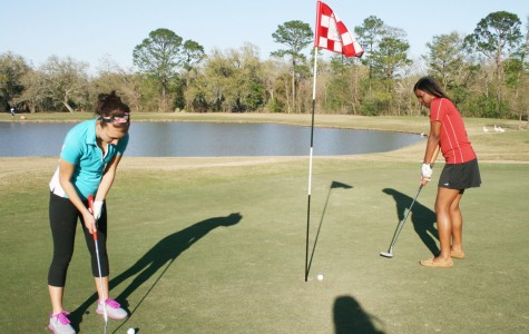 Freshman chemistry major Julia Falco and mass communication junior Raven Richard putt the ball at the end of their round. The two enjoy the challenge that golf brings.