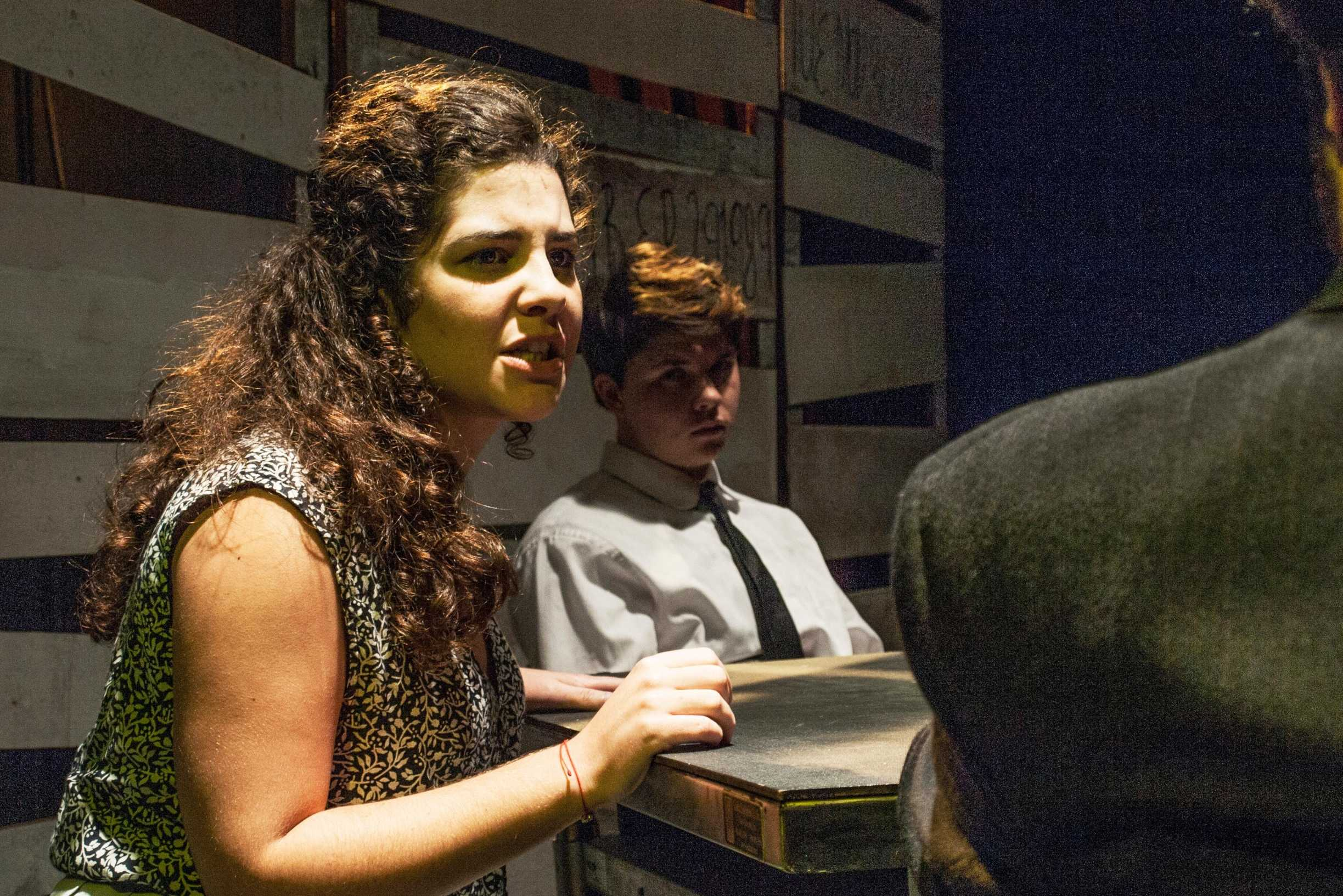 "Alina Gordillo, theatre arts sophomore, is interrogated by a police officer, jazz studies junior Miles Crabtree, in ""The Witness"". The play is a one-act directed by theatre arts senior Rachel Christian and tells the story of the six Jesuits murdered in El Salvador by U.S. trained soldiers."