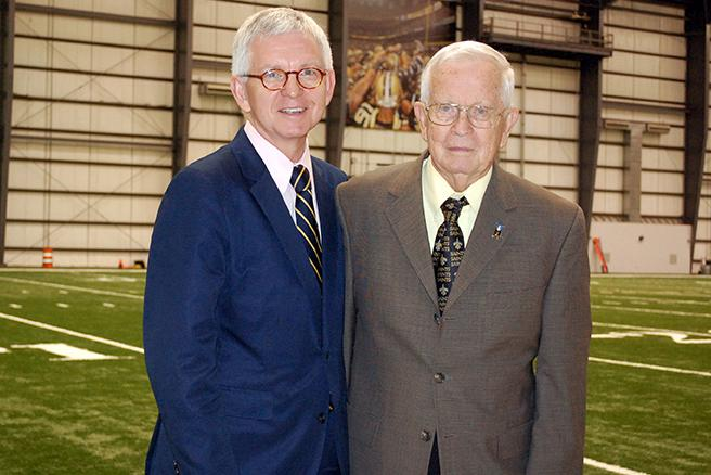 Jerry Romig A '46 (right) stands next to his son, Mark, at the Saint's practice facility. Mark took over for his father as public address announcer at the end of the pre season.