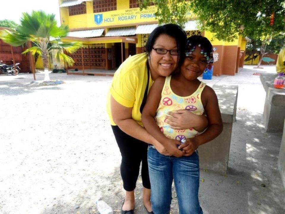Heather Malveaux, director of Immersion Programs for University Ministry, hugs a Jamaican student from Holy Rosary Primary School. In Jamaica, Ignacio Volunteers cared for the destitute and dying and helped teach in primary schools.