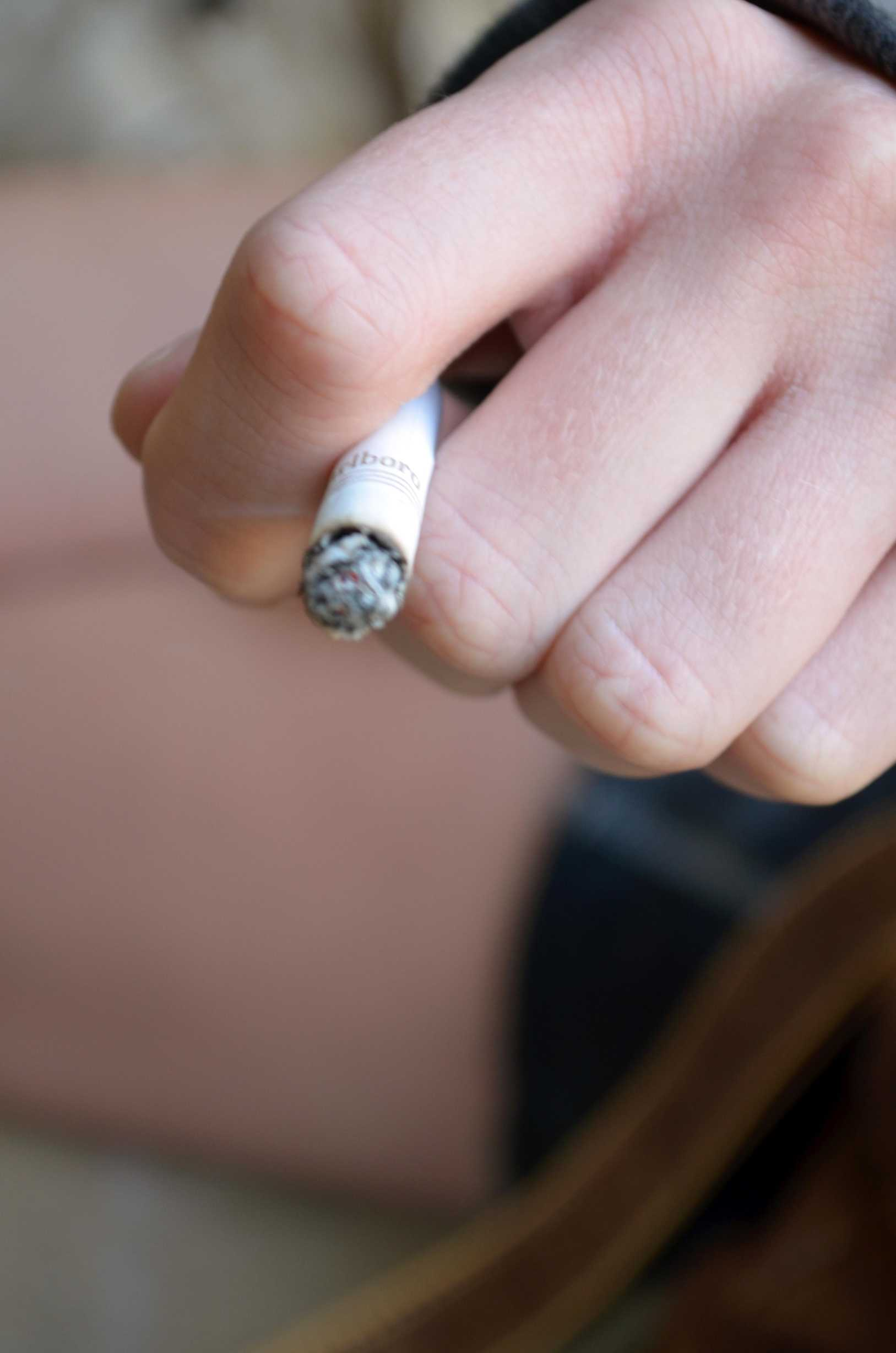 A student lights up a cigarette. Loyola's campus is now non-smoking