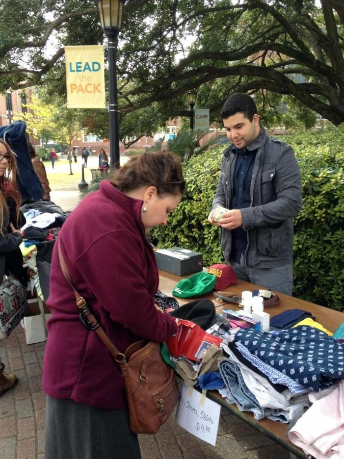 Diane Blair, Loyola Institute for Ministry on-campus services coordinator, purchases a hat from Gabriel Miranda, political science sophomore, at the relief thrift shop.This fundraiser was one event hosted by student groups.