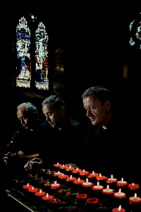 The Priests kneel in prayer. The Irish music group, which has performed around the world, sang at Loyola on November 26.