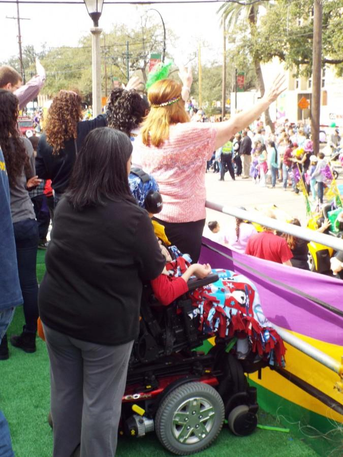 A child and his mother use the Mardi Gras platforms in front of Touro Synagogue at a Mardi Gras parade on Saturday, Feb. 22. Loyola students helped build the platforms as a Mardi Gras service project.