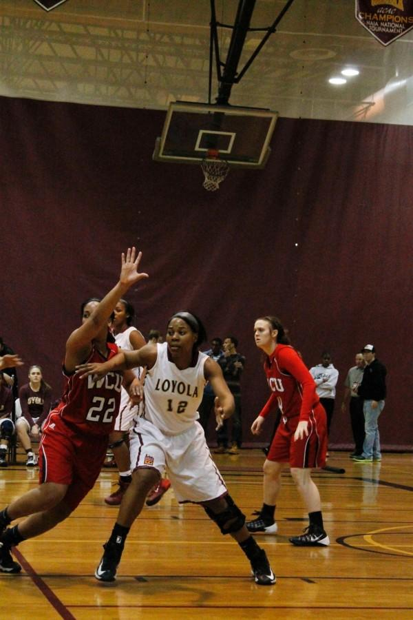 Jasmine Brewer, psychology senior, defends against an opponent on the basketball court. Brewer is a member of Loyola's women's basketball team who was honored with the NAIA Champions of Character Award this year.