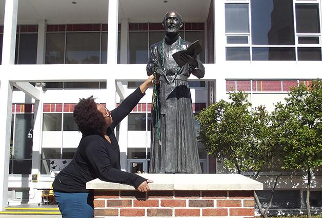 Bethany Washington, business junior, gets the St. Ignatius statue in the Mardi Gras spirit with some beads. Mardi Gras season is not just about the parades and throws, it also contains religious symbolism.