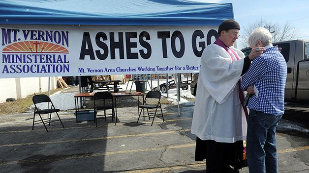 """A priest offers someone ashes in Indiana on March 5, 2014. The """"Ashes on the Go"""" program began in 2010 as a way to bring the Church to people in their daily lives."""