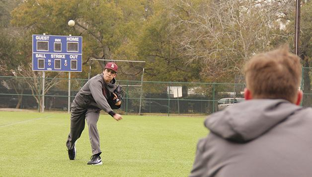 John Daley, accounting freshman, throws a fastball to Head Coach Doug Faust. The men's baseball team is heading into a critical strecth of conference games this month.