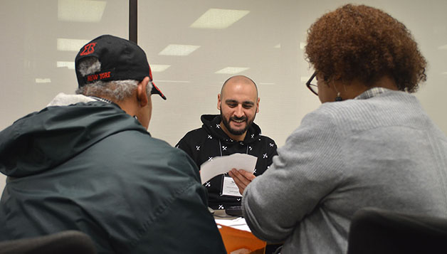 Sergey Garanyants (center), third year law student, helps a married couple during a session at the College of Law's Volunteer Income Tax Assistance program. The VITA program offers free tax preparation for moderate to low-income tax payers and Loyola students.