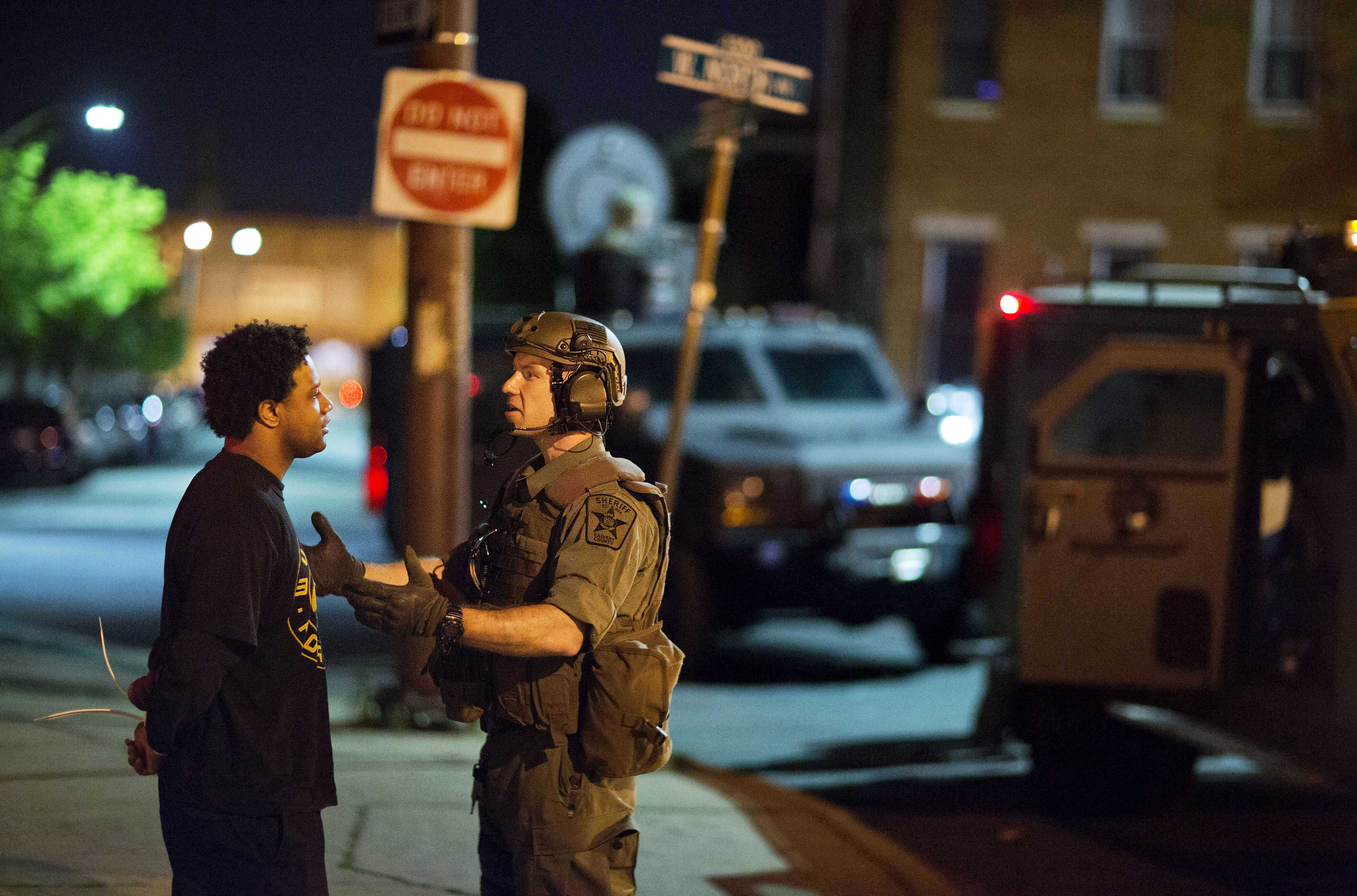A man is arrested for violating the curfew Tuesday, April 28, 2015, in Baltimore. A line of police behind riot shields hurled smoke grenades and fired pepper balls at dozens of protesters to enforce a citywide curfew.