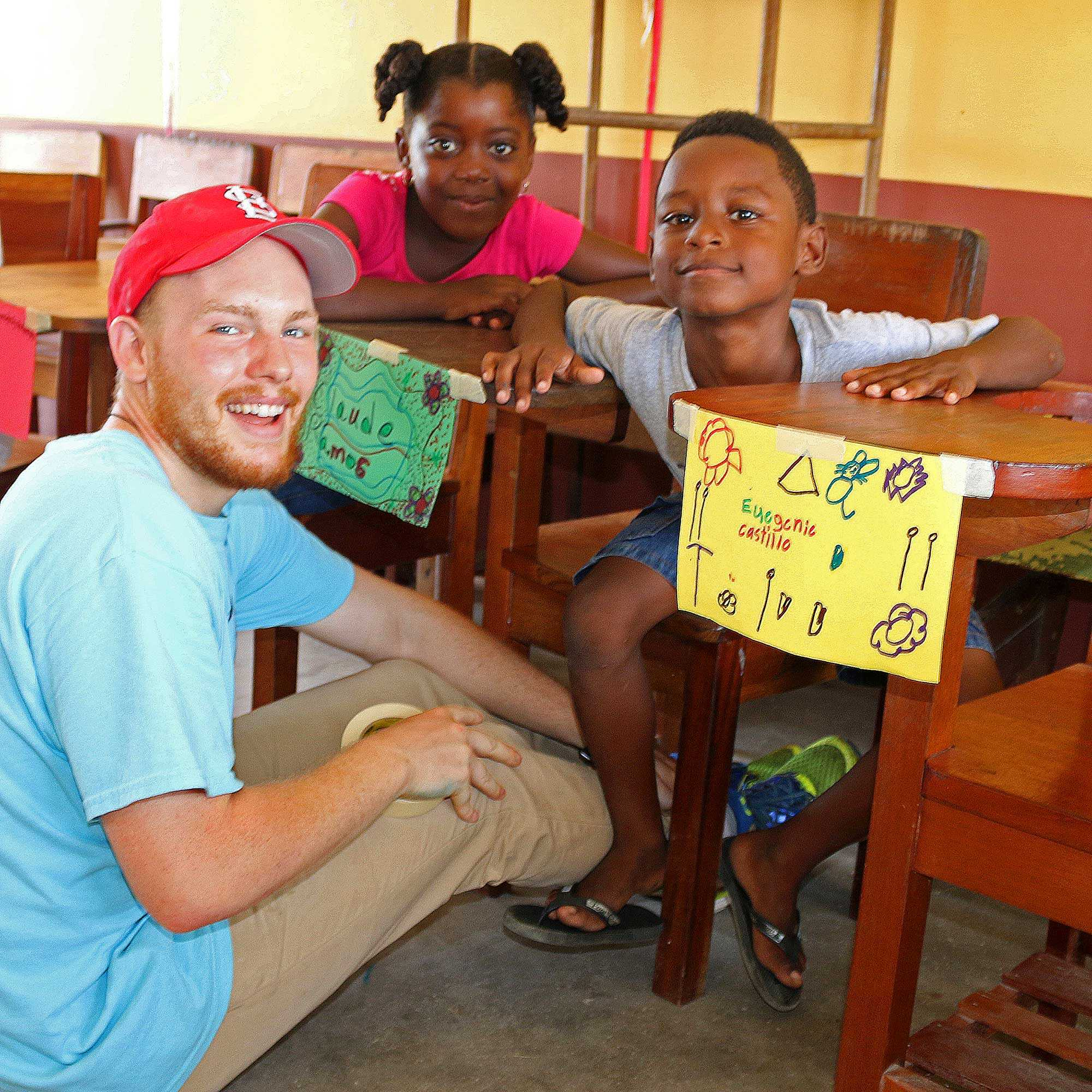 Brendan Dodd, management senior, poses with children during the summer 2015 Iggy Vols trip in Dagriga, Belize. The volunteers spent their time teaching children and learning about the culture
