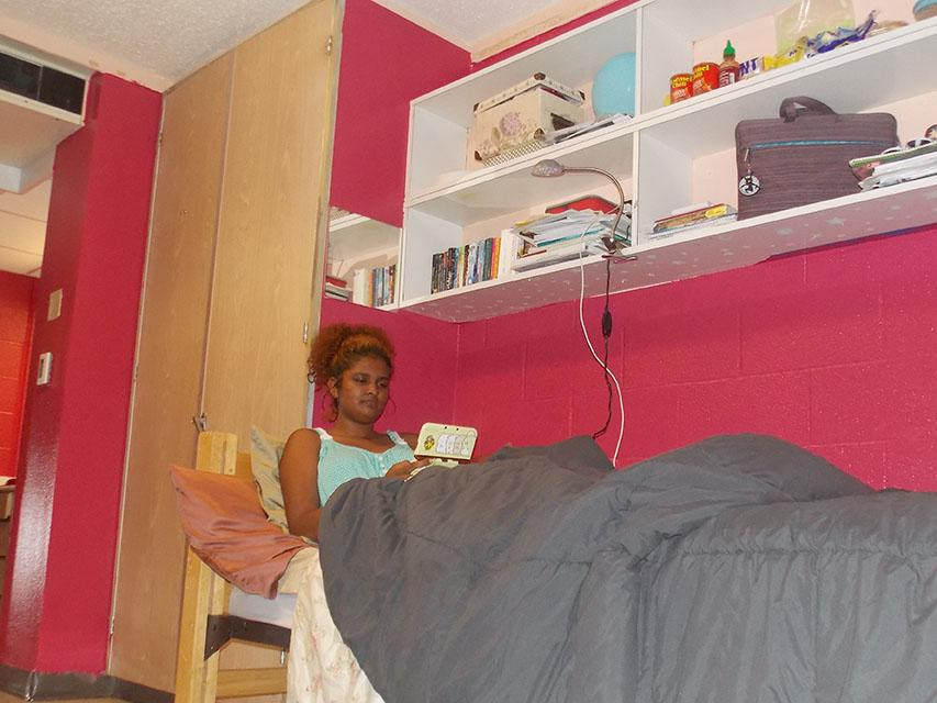 Sophomore Asia Stoll, an international business major relaxes in bed after a long day of classes. Stoll painted her room Raspberry Glaze because of the new Paint Your Own Room program in Buddig Hall.