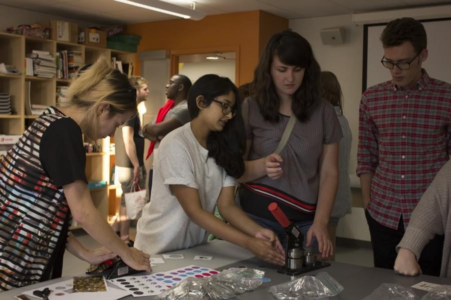 Sierra Lyman, mass communication junior, and Ruvini Wijesekera, graphic design junior, show off the Design Studios button-making machine. Interactive demonstrations in the graphic design department were part of the Monroe Hall open house. Photo credit: Taylor Galmiche