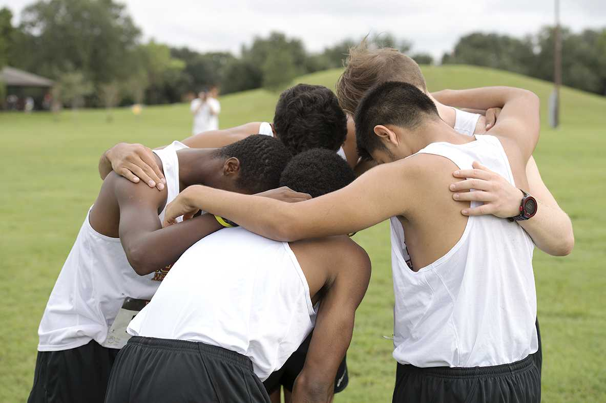 The men's cross country team huddles together before competing in the All-State Sugarbowl Invitational hosted by Loyola University. Both the men's and the women's team placed in the top five at their only home meet of the season, and are looking to continue to build on that success throughout the year. Photo credit: Courtesy of the Athletic Department
