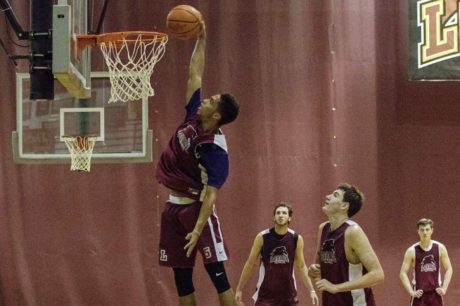 Jalen Gray, a junior forward, dunks the ball during practice. Photo credit: Zach Brien