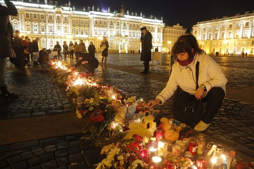 A woman lights a candle in memory of the plane crash victims at Dvortsovaya (Palace) Square in St.Petersburg, Russia, Tuesday, Nov. 3, 2015. Mourners continued to come to St. Petersburg's Pulkovo airport and Dvortsovaya Square on Tuesday to lay flowers and leave paper planes and soft toys at the arrivals hall. (AP Photo/Dmitry Lovetsky)