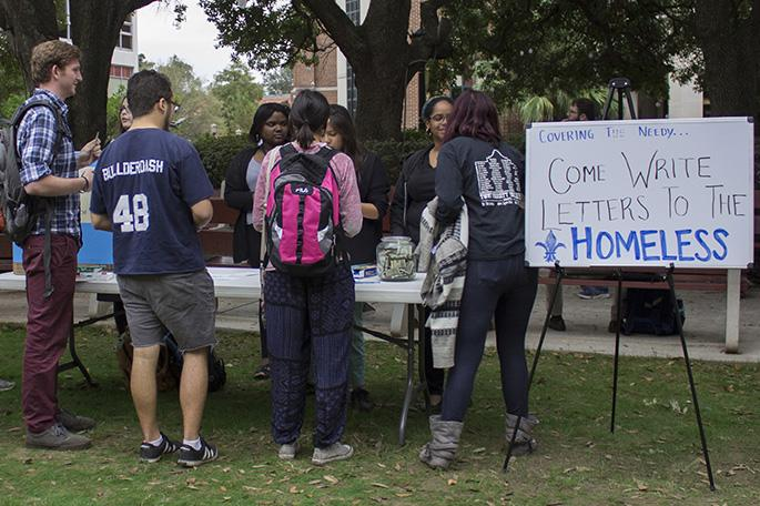 """Loyola students write letters to the homeless at """"Covering the Needy"""" in the Peace Quad on Nov. 12. The event raised money to provide blankets for homeless New Orleanians."""