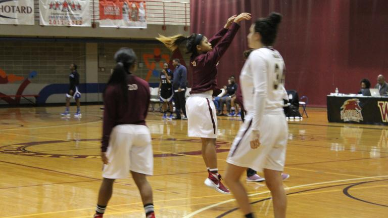 Guard Zoie Miller, mass communication sophomore, takes warm up shots at halftime of their game versus Dillard on Dec. 5, 2015.