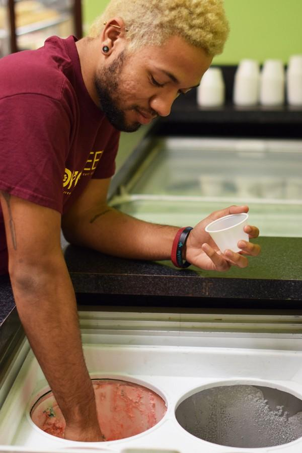 Christian Williams, biochemistry freshman, scoops ice cream in the Orleans Room. Blue Bell ice cream used to be served at Loyola, until it was recalled last year. Photo credit: Molly Olwig