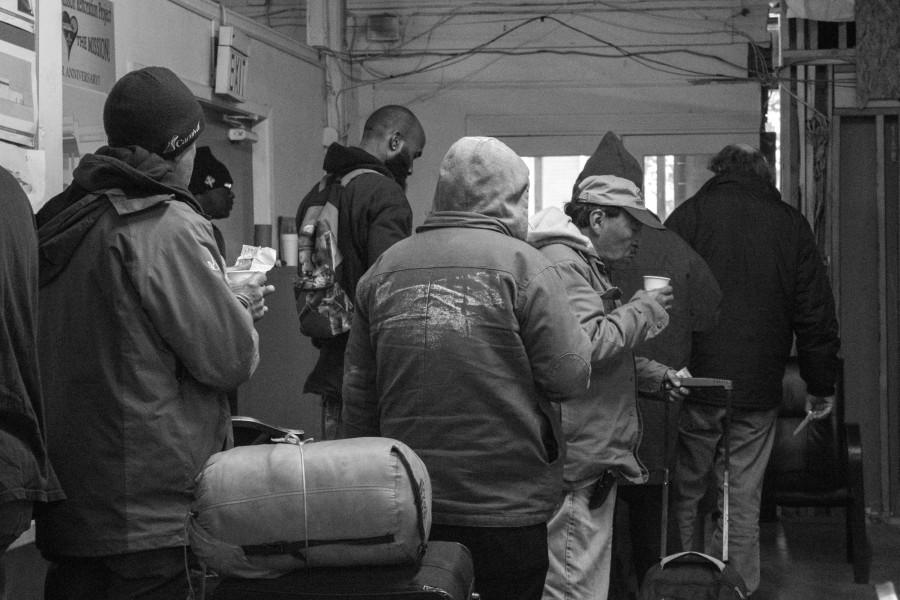 Men line up in their designated check-in line. Michael Smith takes their names for documentation. After check in the men continue to the chapel for a hot cup of coffee. Jan. 22, 2016.