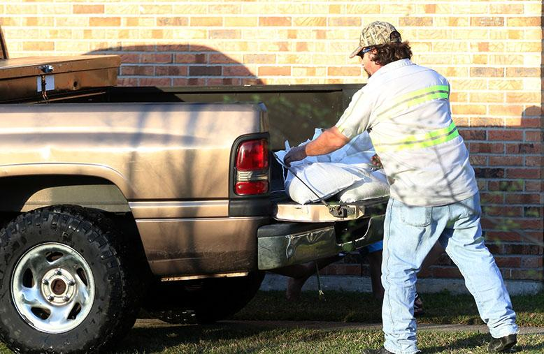 A man unloads sand bags from his truck to place around his home in Slidell, Louisiana on Monday, March 14, 2016. Residents in Slidell were concerned about flooding in the area after a weekend of heaving rain and flooding across Louisiana and the Pearl River cresting.