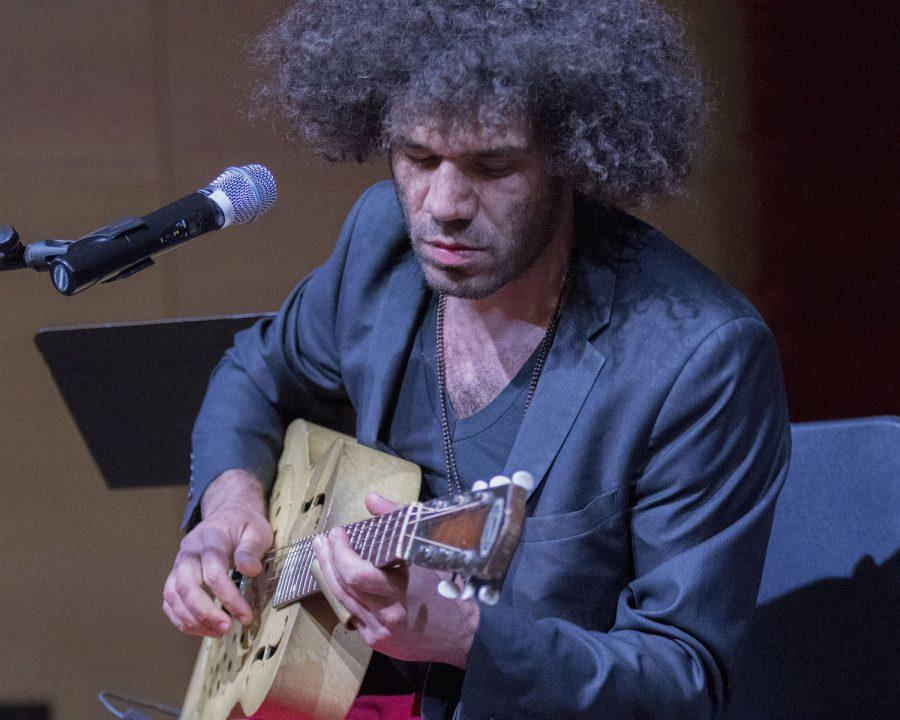 Johnny Azari, Delta blues musician, plays his guitar during the Syria and Beyond Refugee Benefit in Nunemaker Auditorium on Wednesday. The event, which was a part of the eighth annual peace conference, benefited The American Refugee Committee, Catholic Relief Services and Doctors Without Boarders.