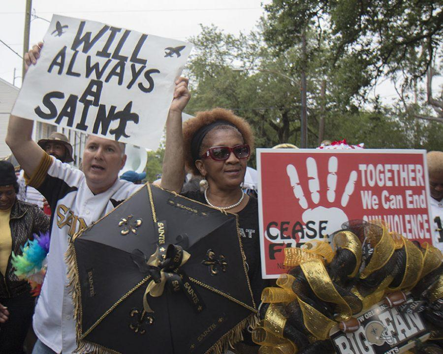 Larry Rolling, left, and Duchess Hearst, right, parade down Camp street in the Lower Garden District as part of the second line for Will Smith on April 15. Smith, a former New Orleans Saint, was shot killed in an altercation after a minor traffic accident in the Lower Garden District on April 9.