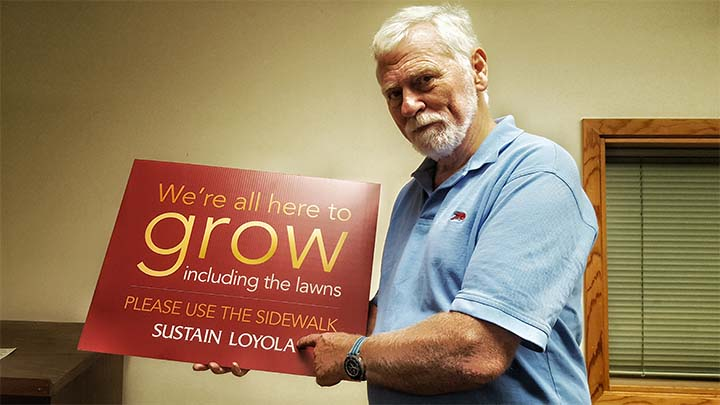 Bob Thomas, holds signs that will be featured around Loyolas campus. The Loyola Sustainability Committee urges people to use the sidewalks to protect the grass.