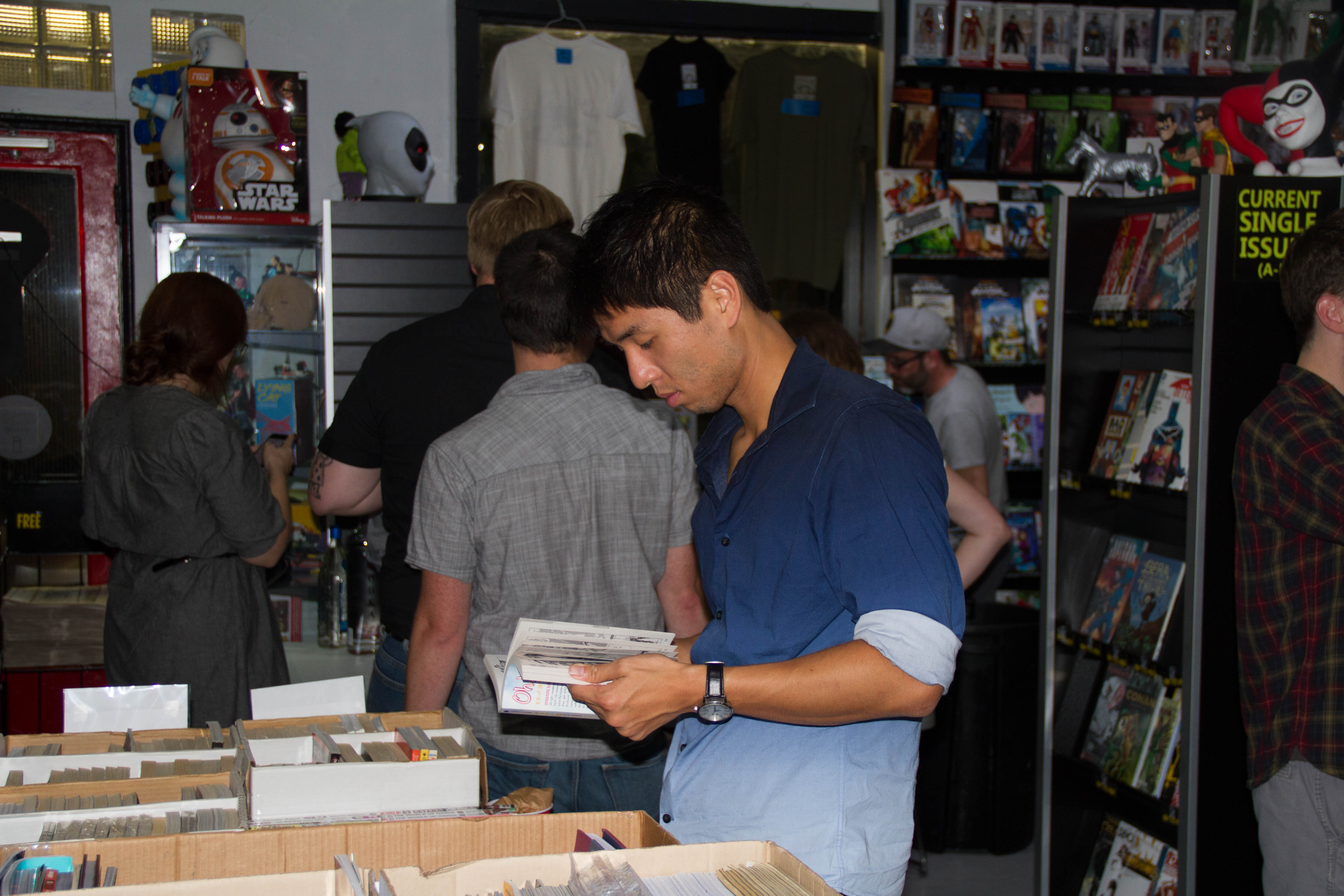 Michael Ho looks through some of the Manga included in the sidewalk sale for $3.