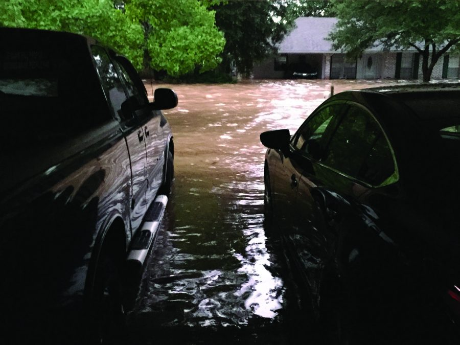 Floods rise against Michele and Kristopher Ellis' cars in their garage and along their street in Baton Rouge, La.
