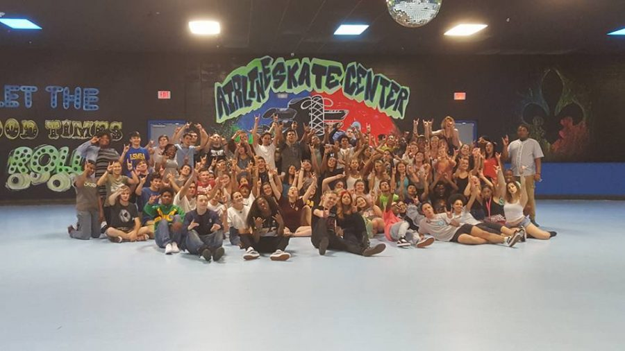 A freshman orientation group raises its Wolf Pack signs at Airline Skate Center during summer 2016. Nighttime outings are a main feature of Loyola's orientation sessions. Photo credit: Nicholas Morea