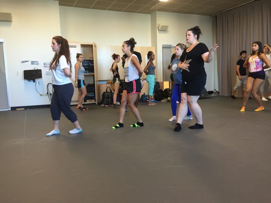 Kadar (in black) demonstrates a Suzuki movement exercise as her class practices.