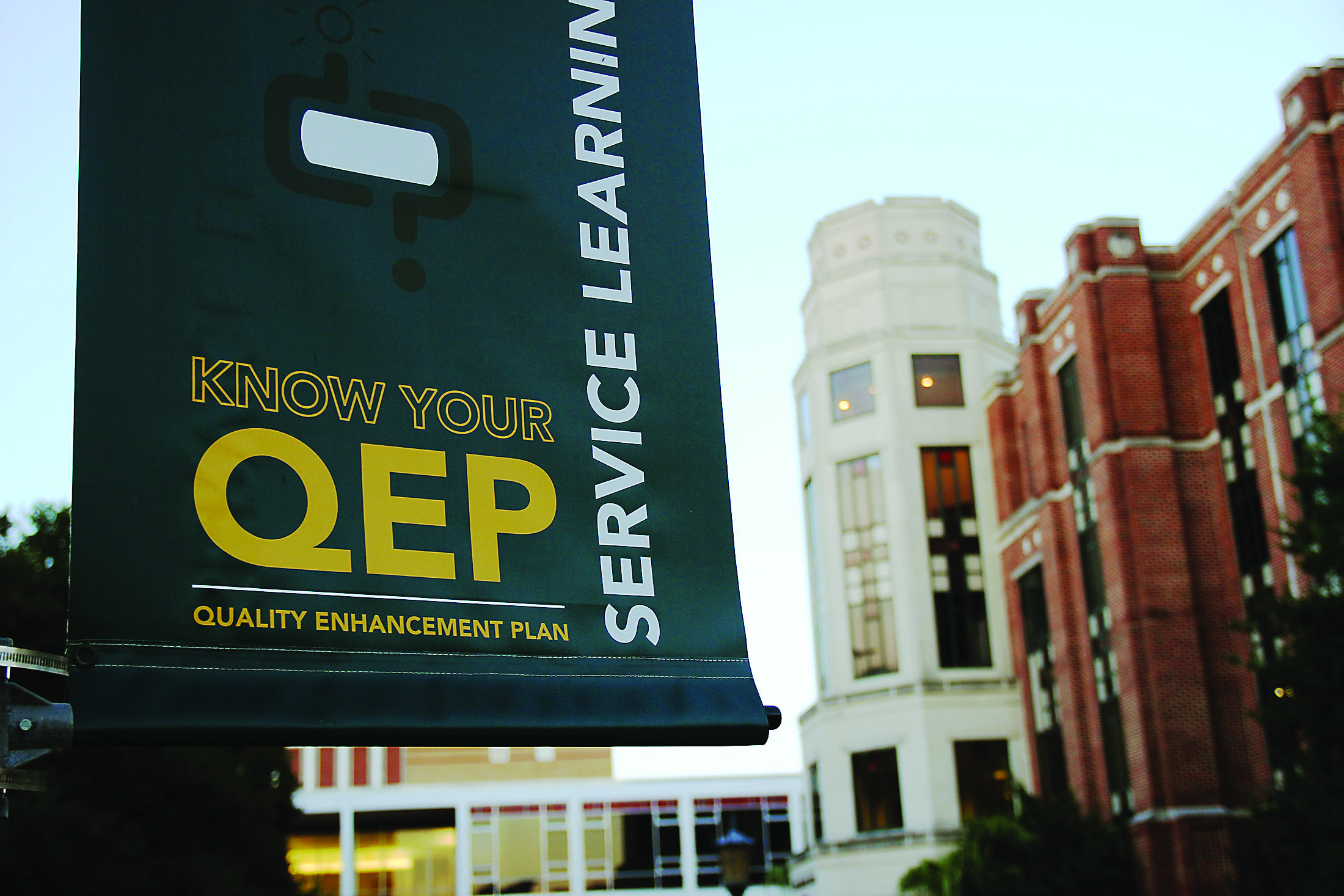A Quality Enhancement Plan banner hangs from a light post in the Peace Quad early this semester. The plan is already being implemented in some classes, with more to come. Photo credit: Tasja Demel