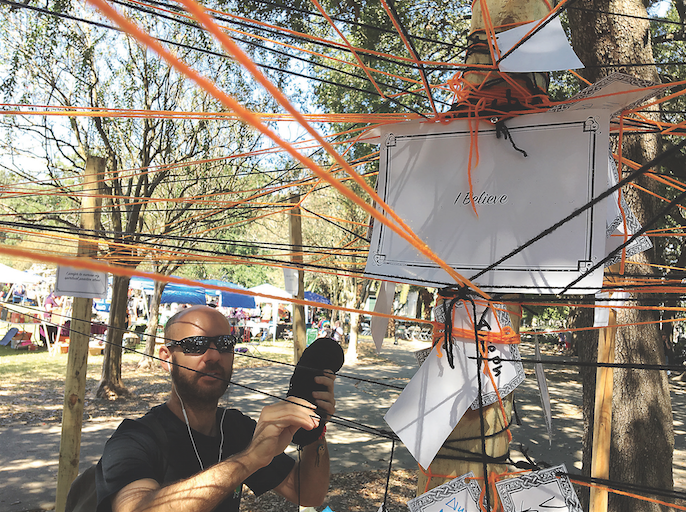 A festival attendee adds his own yarn to the faith web, Pagan Pride Festival's first ever art installation. The festival gave people an opportunity to gather and discuss their beliefs.