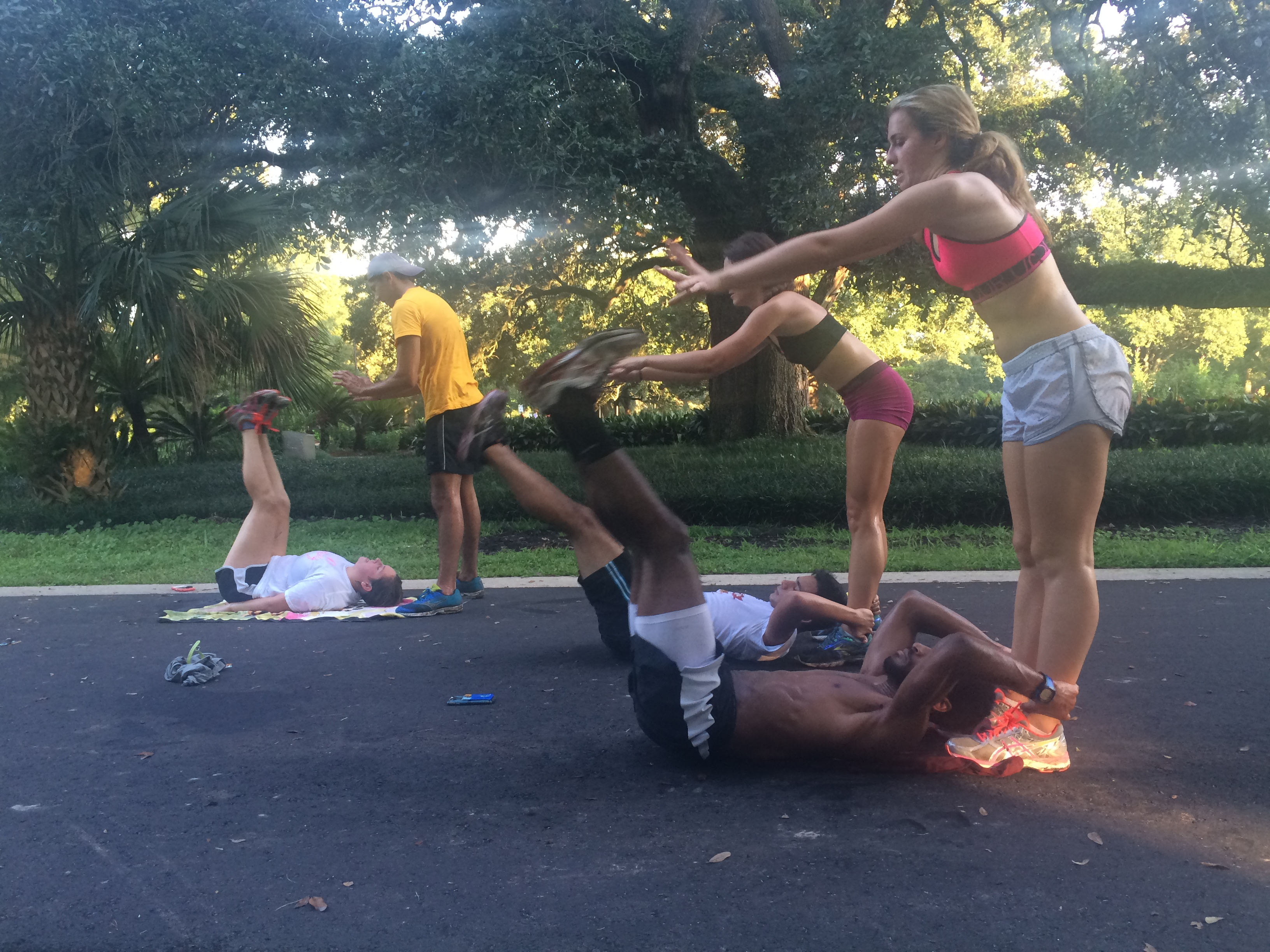 The cross country team does ab exercises after a run in Audubon Park in late August. The team finished the season with new records and few injuries. Photo credit: Colleen Dulle