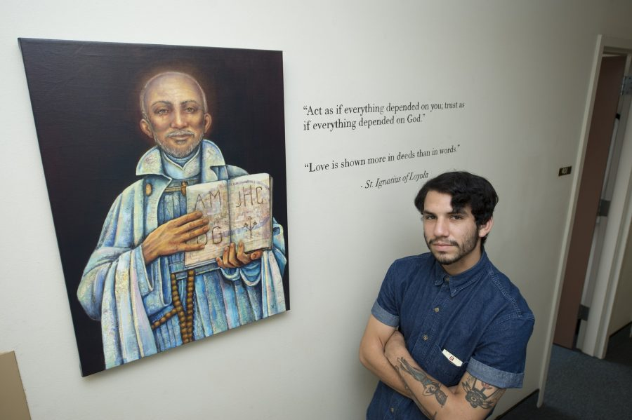 Design+senior+Andres+Arauz+poses+with+%22Ignatius%22+painting+created+by+Holly+Schapker.The+original+artwork+is+one+of+a+series+of+paintings+by+Schapker+related+to+Ignatian+Spirituality.+Photo+credit%3A+Lindsay+Horn