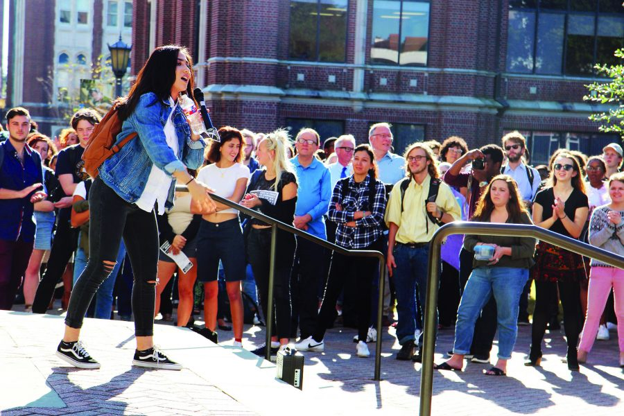 Melissa Alba, political science junior, talks to a crowd outside Monroe Library about her experiences as a Hispanic American in the U.S. She addressed members of the Loyola community as part of the campus' solidarity walkout staged Nov. 16. Photo credit: Tasja Demel