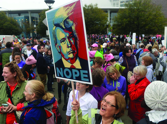 Liliana Wendorff holds a sign at First Ward Park during Saturday's Women's March on Charlotte, N.C., which drew at least 10,000 people according to CMPD. The mile-long march was scheduled to coincide with a national demonstration Saturday, Jan. 21, 2017 in Washington, D.C., the day after Donald Trump's inauguration as president. The march started at First Ward Park, traveled down Tryon Street to 4th St. to Church St. and ended at Romare Bearden Park.